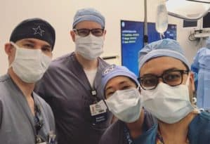 Residents wearing masks in operating room