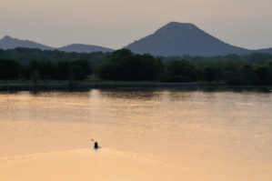 Lone person canoeing on a lake at sunset or sunrise in front of Pinnacle Mountain in Little Rock.