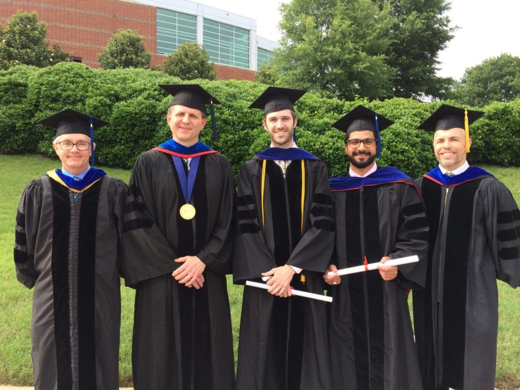 Biochem 2017 Grads - five people wearing academic regalia outside at commencement ceremony