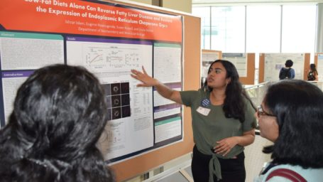 student explains research poster