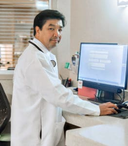"""A picture of Dr. Feliciano """"Pele"""" Yu standing at a computer"""