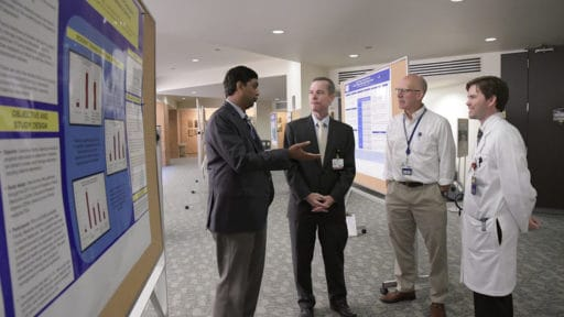 Faculty discussing next to poster presentations
