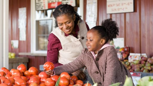 grandmother and granddaughter selecting vegetables at a market