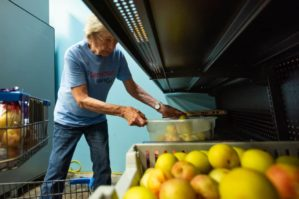 Woman places a case of fresh fruit on a shelf