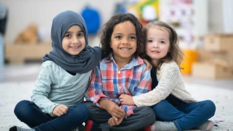 Two girls and a boy are indoors in their preschool classroom. The multi-ethnic group is smiling at the camera while sitting on the carpet and embracing. One girl is Muslim and she is wearing a hijab and the other girl is Caucasian.