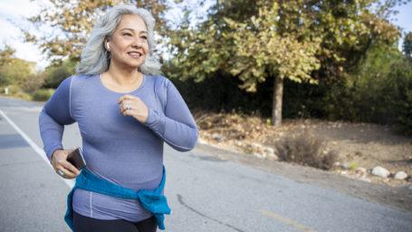 A mature Latina woman jogging on a trail