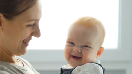 Mom and baby laugh together.