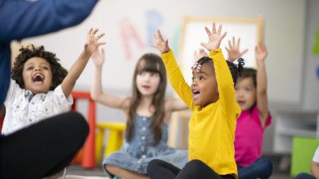 Daycare children raising hands enthusiastically