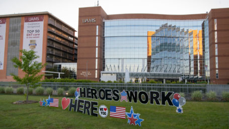 Exterior of UAMS buildings with Heroes Work Here lettering on the lawn