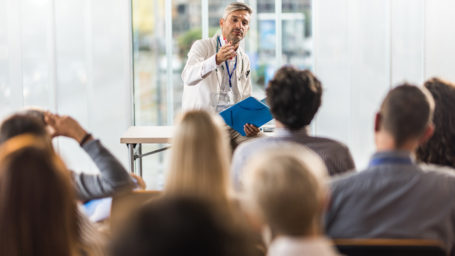 Male doctor talking to large group of people on a seminar in a board room.