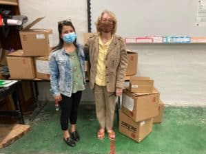 Two women posing beside boxes of scientific equipment