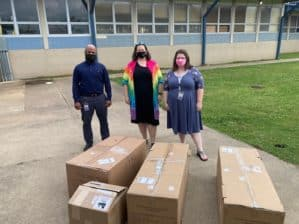 Three people posing outside a school with boxes of scientific equipment