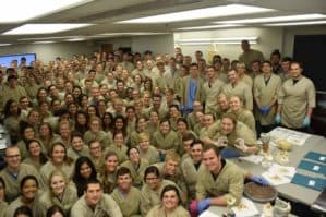 Group photo of an M1 class wearing gross anatomy lab coats and scrubs.