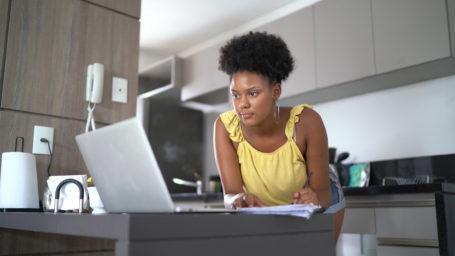 Teenage girl using laptop studying at home