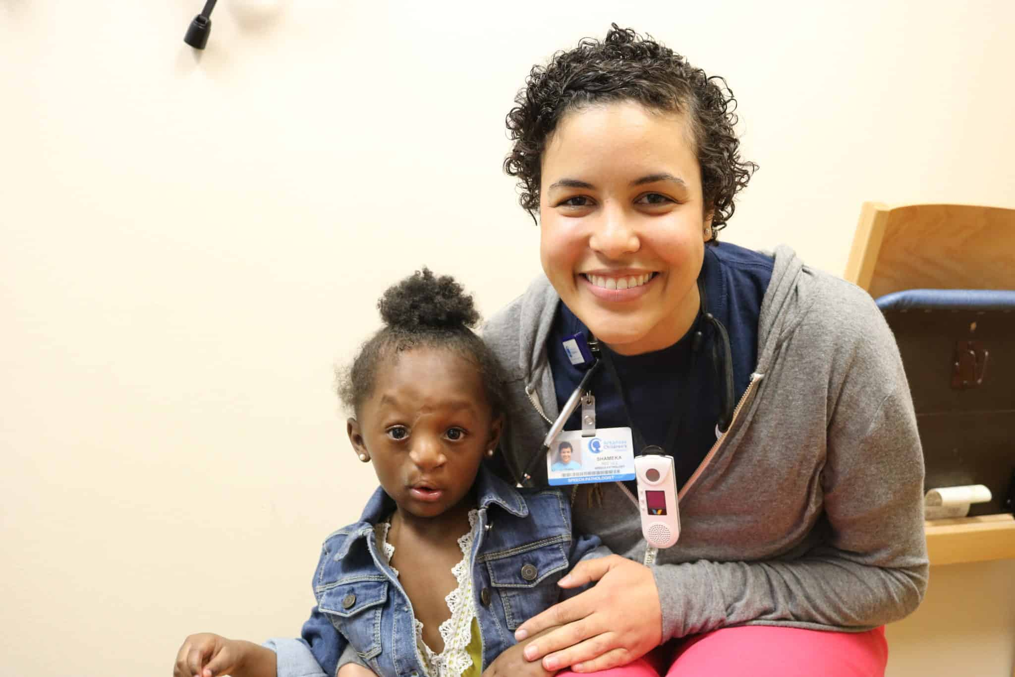 Patient 2 at 2 years old with speech pathologist Shameka Reeves.
