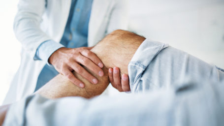 Close up image of a doctor examining a patient's knee