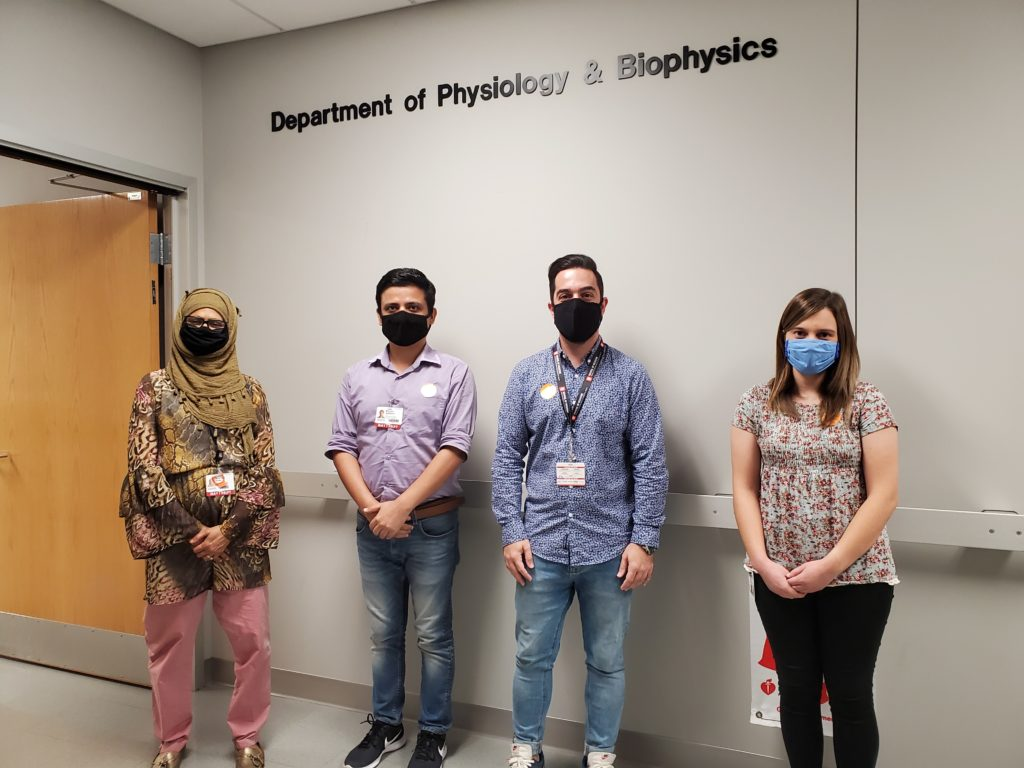 Dr. Delgado-Calle standing with lab members in a hallway. All are wearing masks.
