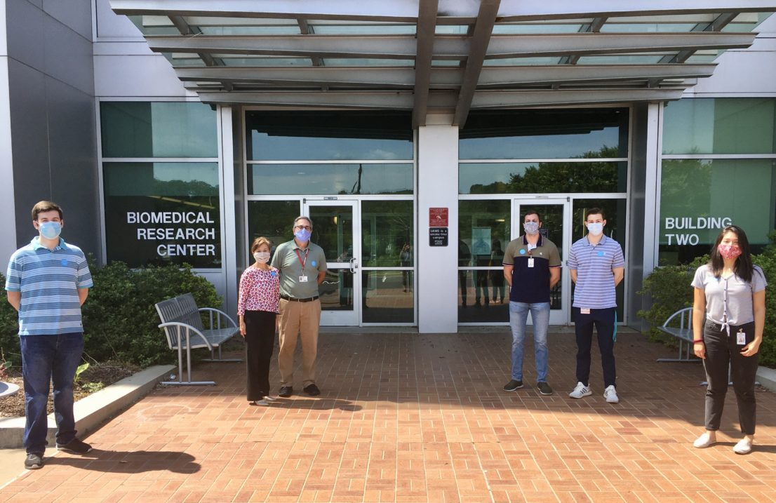 Lab group wearing masks outside Biomedical Two building