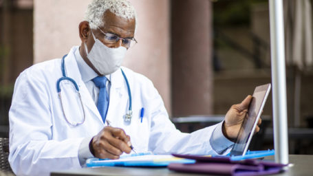A senior African American doctor using a tablet and clipboard filing a report wearing a mask