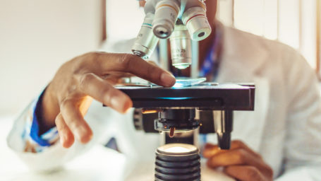 African-American men in a laboratory microscope with microscope slide in hand.