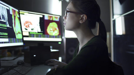 Close up image of a young asian woman working at a desk with multiple monitors. The monitors contain MRI and other information.