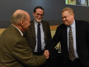 Three men; man on left shaking hands with man on right