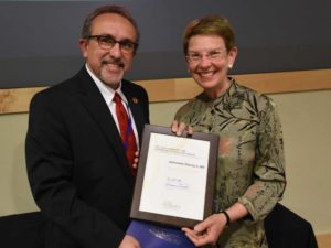 Man and woman holding award certificate