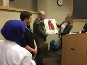 Student presents a painting to faculty members.