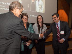 Dr. McDonald presenting awards to team