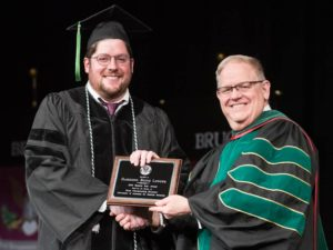 Student holding award, shaking hands with faculty member