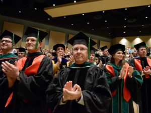 Faculty members in regalia, clapping