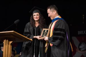 Student presenting plaque to faculty member