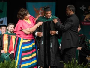 Two people assisting student put on regalia hood over gown