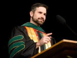 Speaker in regalia at podium