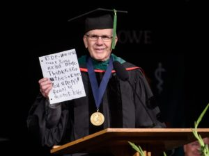 Dr. Westfall at podium holding note
