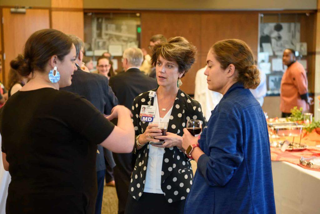 Faculty talking at a reception