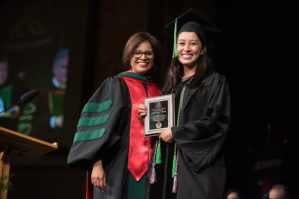 Dr. Tariq awarding a plaque to a student at Convocation