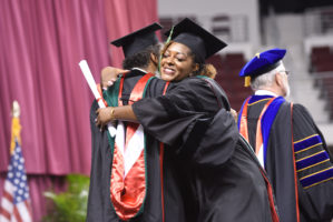 Female African American student hugs a professor after receiving her degree at convocation