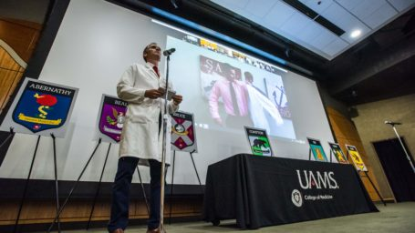 White Coat Ceremony from 2020, faculty member in white coat watches student on screen