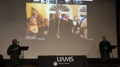 Two professors on stage in front of a screen that is showing a student at home being hooded by family