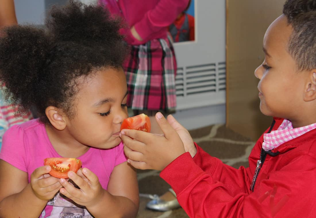 two children smelling a tomato